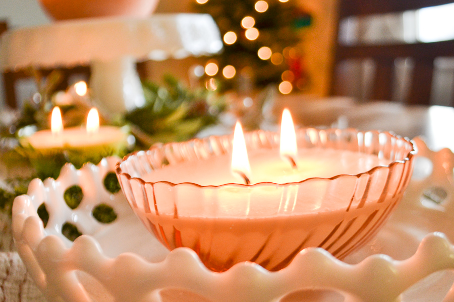 A close up of a pink depression glass candle in a white milk glass tray