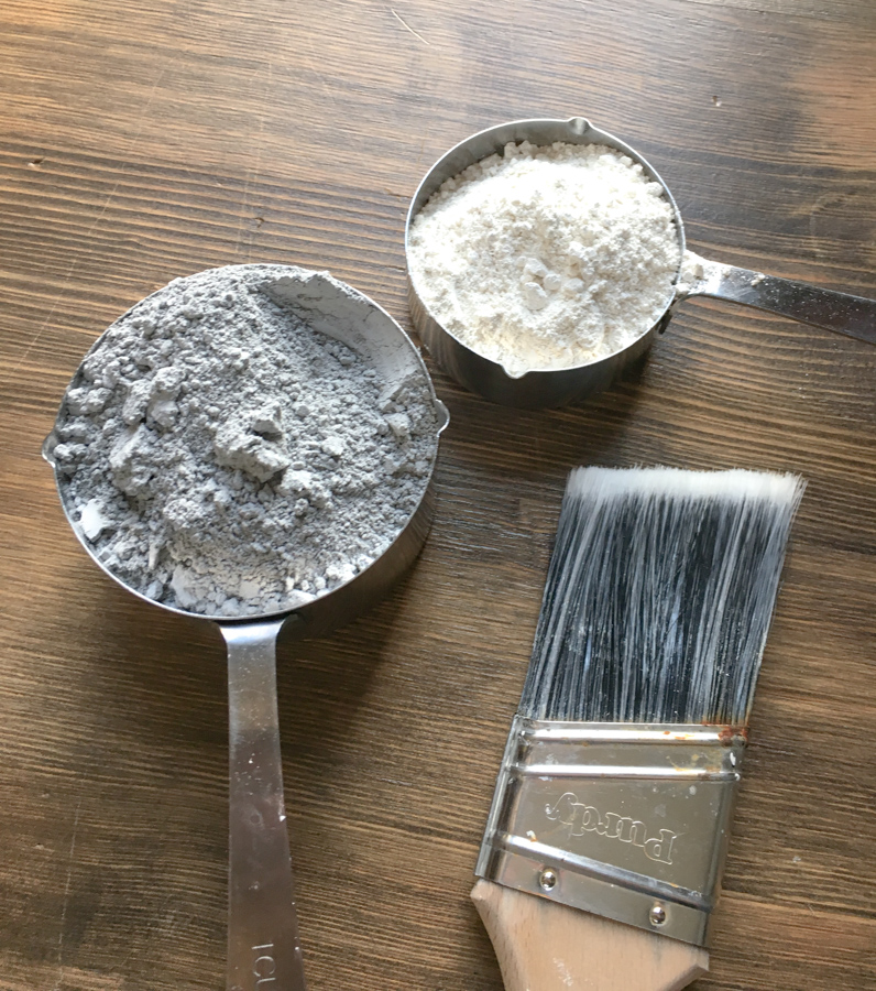 A close up of two measuring cups on a wood surface with the top part of a paint brush