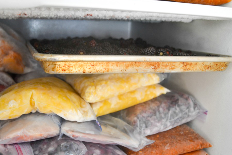 A close up of a cookie tray in a freezer sitting flat
