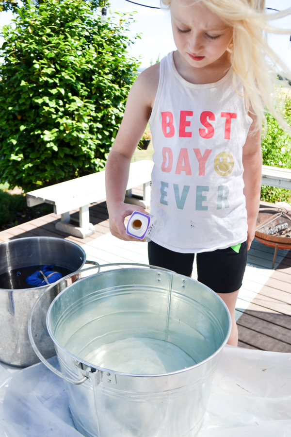 A young blonde girl pouring a color stay additive into water
