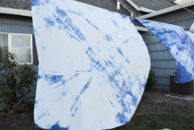 A Shibori tie dye linen towel hanging on a clothesline