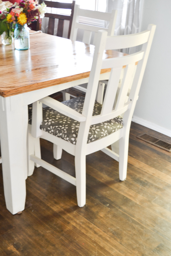 A close up view of a white chair pushed in at a dining room table with a dark floor and a light colored tabletop with white legs
