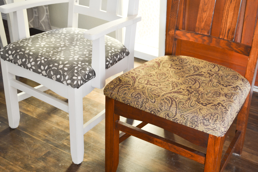 A close up of two chairs, one painted white with a blue and white fabric seat and the other brown with a brown damask fabric seat