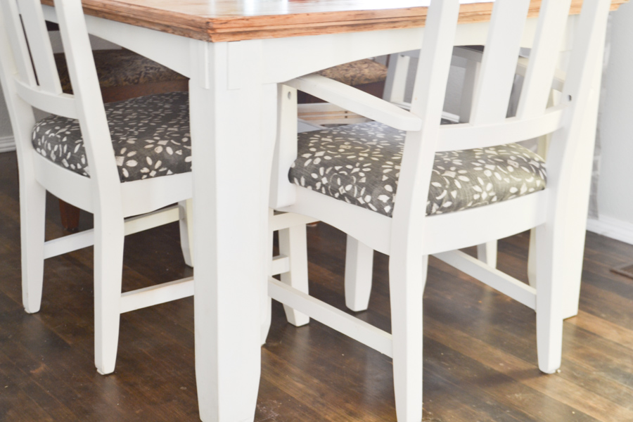 A close up of two chairs painted white with blue and white fabric pushed under a table