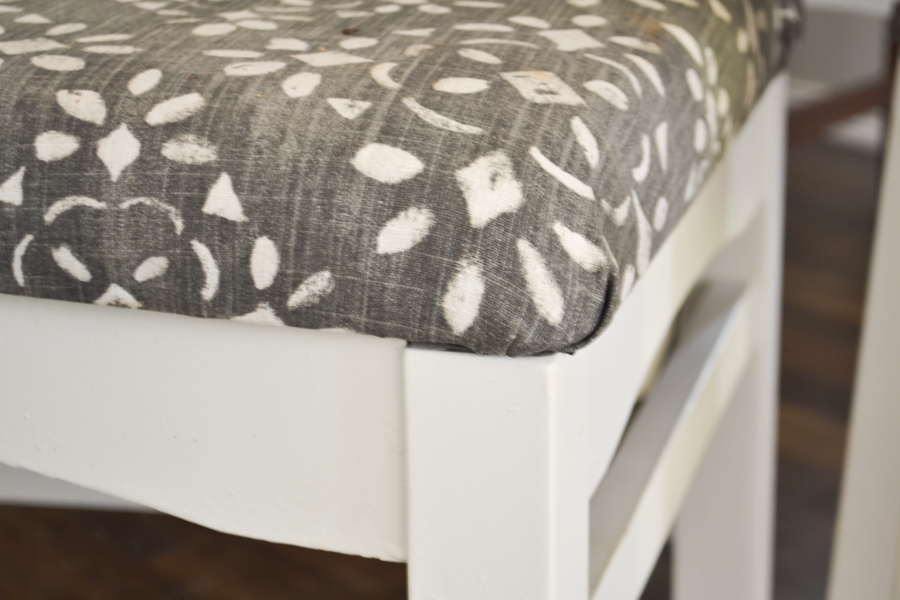 A close up of the corner of a dining room chair with a denim and white fabric pattern on a white seat