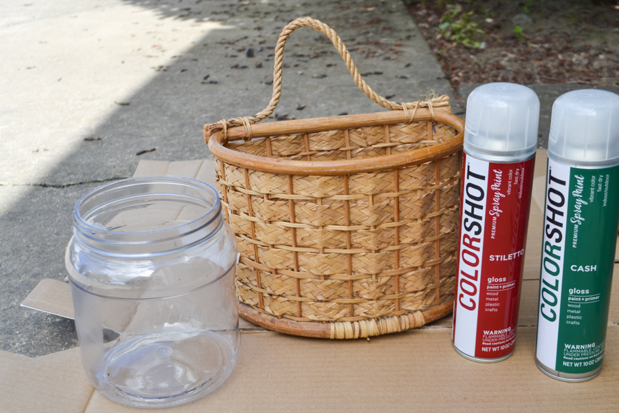 A brown basket with a hanger sitting on a piece of cardboard with two cans of Colorshot spray paint, green and red sitting next to it and an empty plastic container on the other side