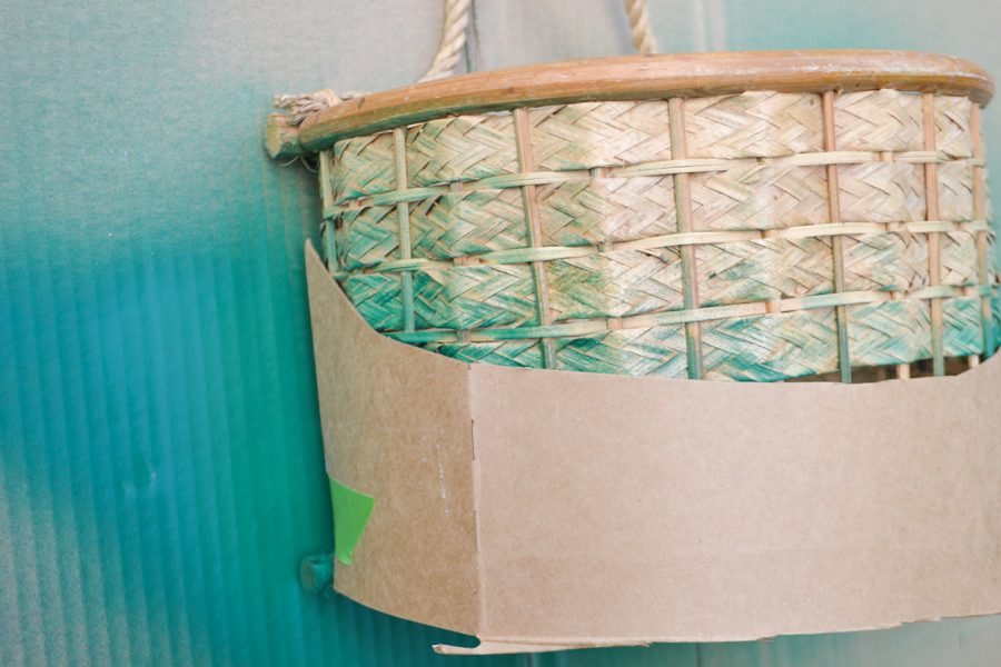 A close up of a basket with half covered in cardboard and the top half unpainted