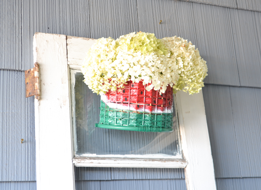A basket painted with red, white and green to look like a watermelon hanging on an old white door against a blue house