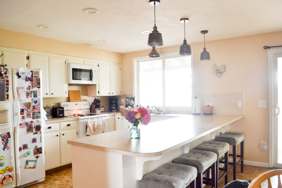 Facing a kitchen island with pendant lights and a window with a microwave and stove on the left
