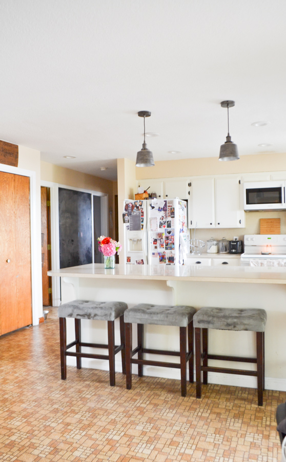A side view of a kitchen with a fridge in the middle, brown pantry doors to the left and an above the stove microwave on the right