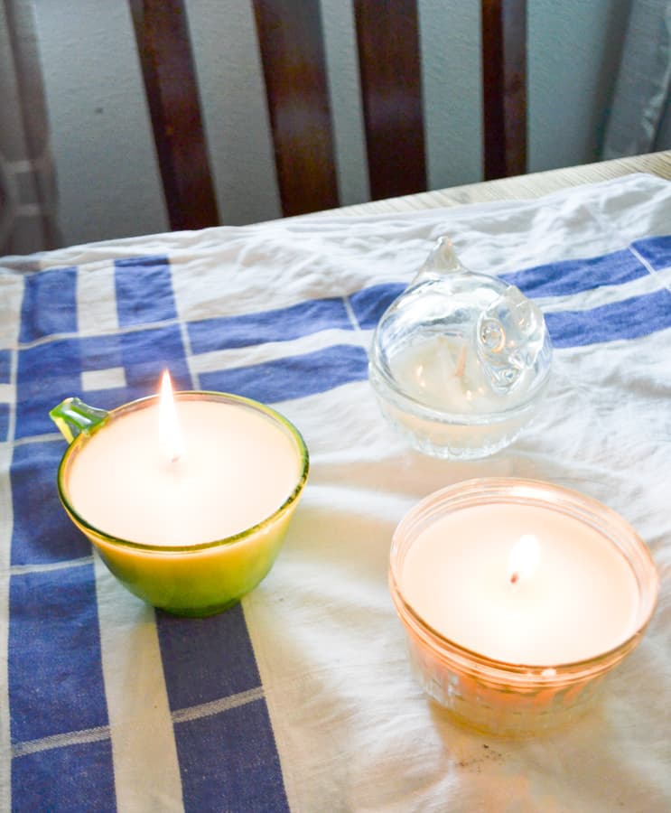 An above view of a glas chicken and two glass soy candles burning on a blue and white tablecloth
