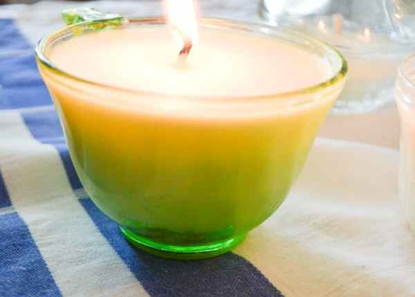 A close up of a burning soy candle in a green depression teacup glass with a glass chicken in the background sitting on a blue and white tablecloth