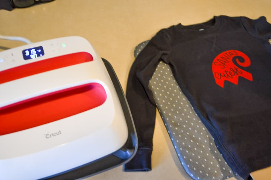 A heat press on the left with a child's black shirt on the right with an elf hat ironed on