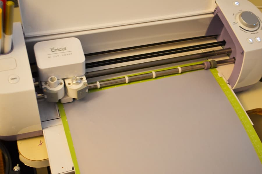 A Cricut cutting machine with a gray iron on being cut