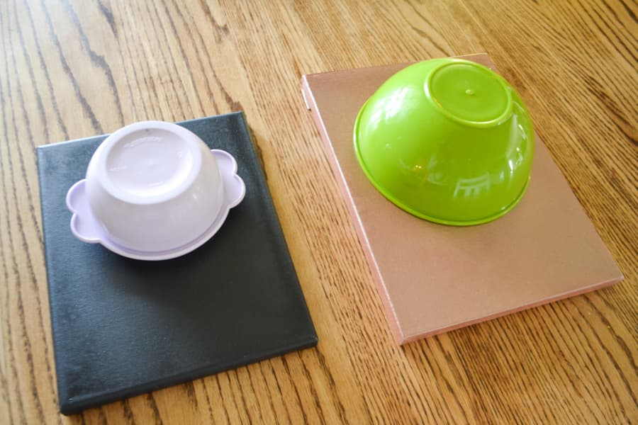 Two spray painted artists canvases, one black and one copper sitting on a light tabletop with a purple and green bowl turned upside down