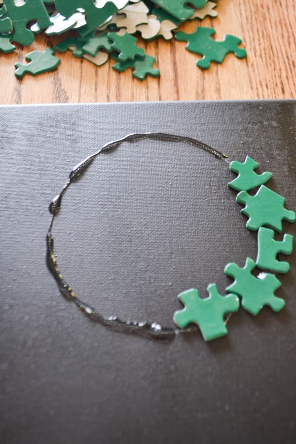 A black painted canvas with a circle of glue with part of it covered in green painted puzzle pieces