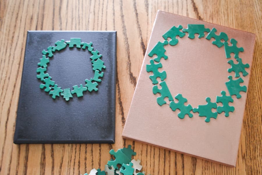 A black and copper painted canvas laying on a table with a green circle of puzzle pieces on each canvas in the shape of a wreath