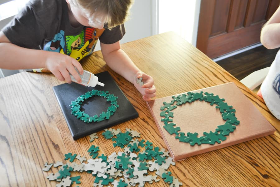 A boy with a glue bottle in his hand applying glue to a wreath shape with a pile of puzzle pieces in the middle of a table
