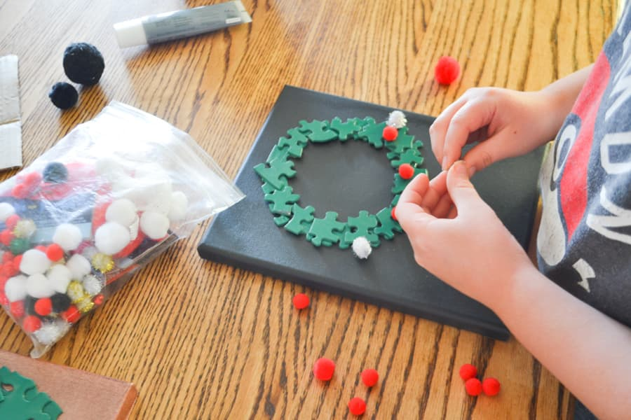 A boy gluing red and silver pom poms on a green puzzle piece wreath