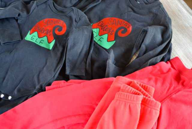 A close up of two black shirts with an elf hat that says Santa's cutest elf with a pile of red pants to the right