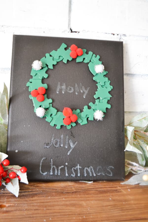 A close up of a black art canvas with a wreath made out of puzzle pieces with pom poms for berries and the words holly jolly Christmas written in a child's handwriting