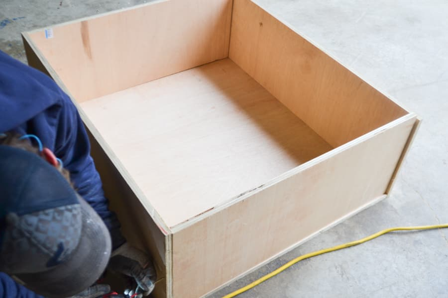A plywood box screwed together laying on a concrete floor