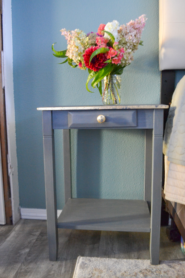 A gray blue nighstand with a drawer with a gold knob and gold trim around the top