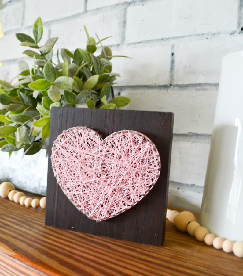 A pink string art heart on a dark wood board sitting on a mantel with wooden beads and a plant behind