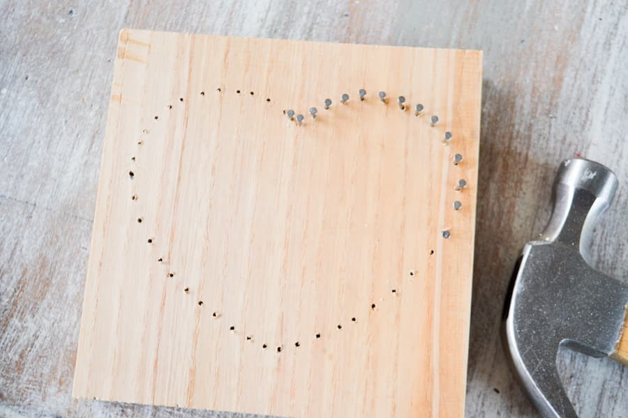 An above view of a heart shape on an unfinished piece of wood with nails in part of the board in the shape of a heart