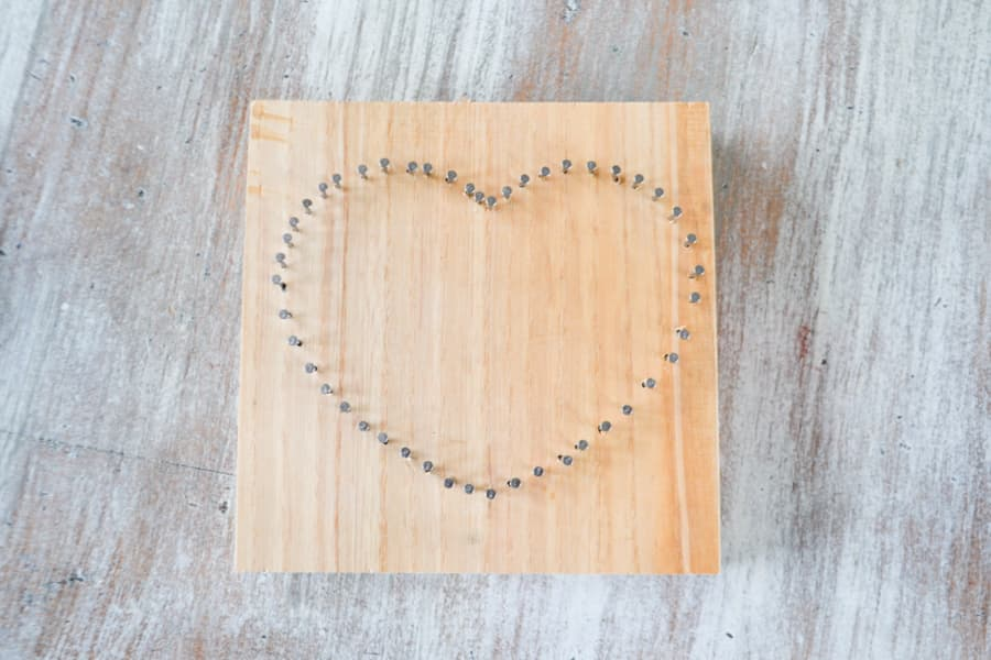 An above view of a finished heart out of nails in a piece of unfinished wood
