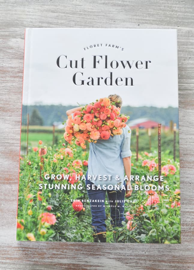 """A close up of the cover of the book """"Cut Flower Garden"""" on a whitewashed tabletop"""