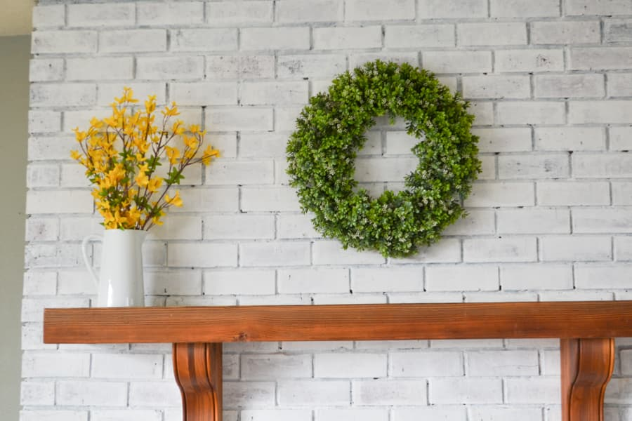 A brown mantel against a white fireplace with a boxwood wreath in the center and a white pitcher with yellow forsythia on the left