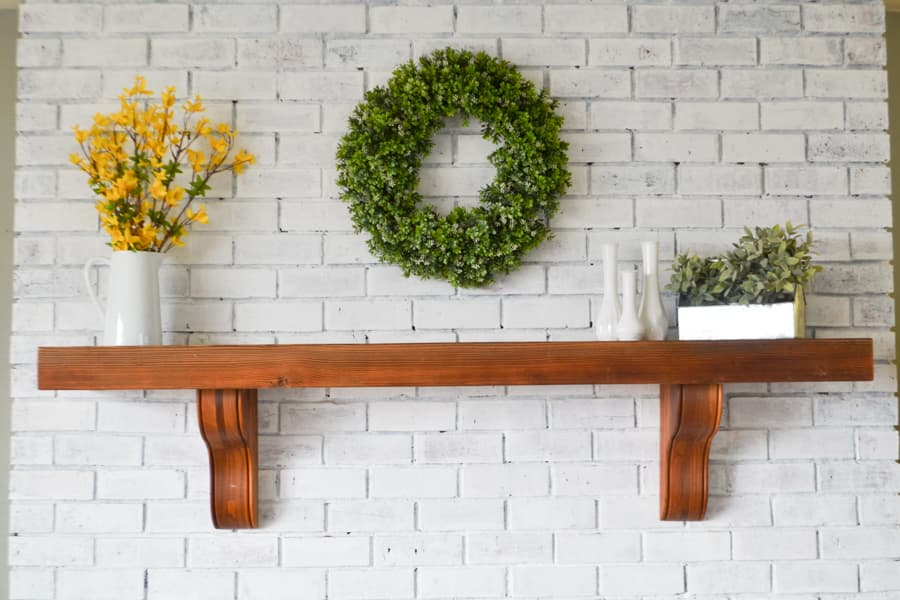 A brown mantel against a white brick fireplace with a white pitcher with yellow branches on the left and a tin container with fake greenery in it on the right