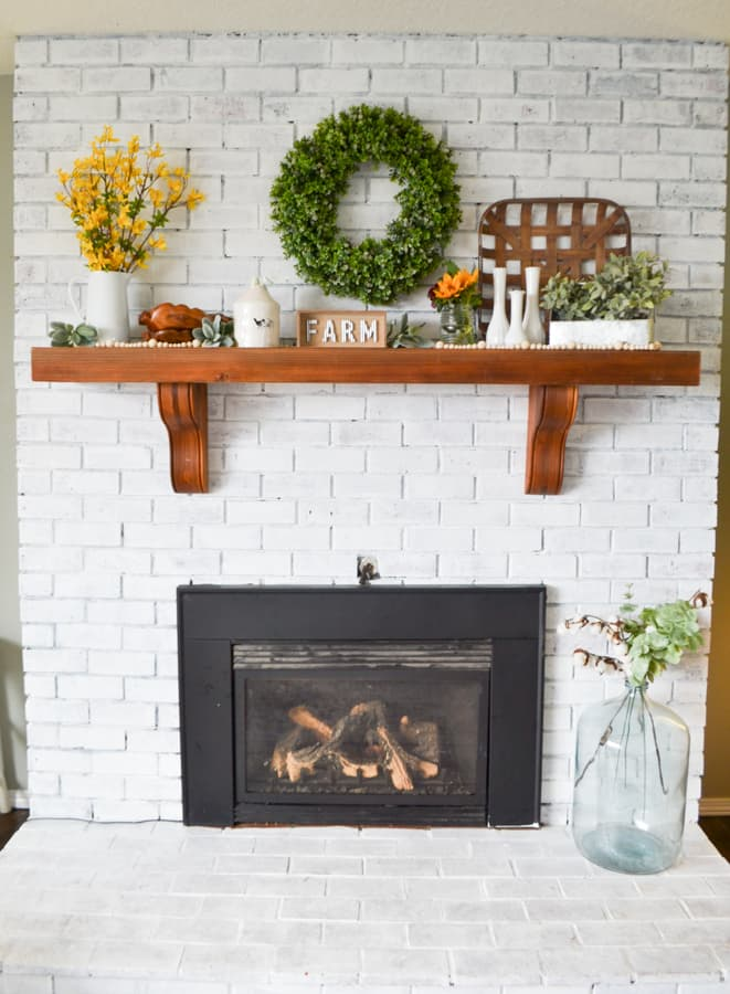 A white brick fireplace with a brown mantel and a black fireplace insert with flowers and multiple arrangements on top