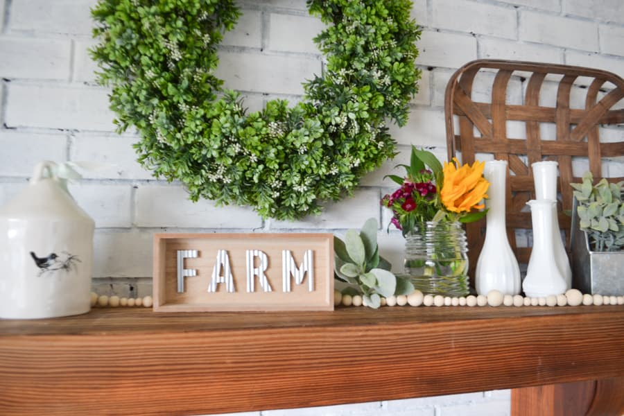 A close up of a brown mantel against a white brick fireplace with a green boxwood wreath with a wood sign that says farm and a bouquet of yellow and purple flowers and white vases on the right