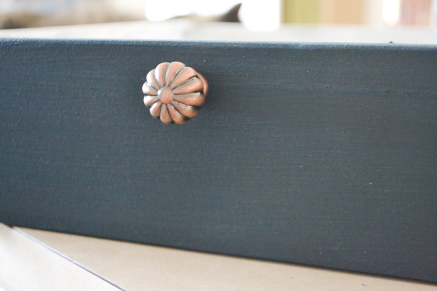 A close up of a blue painted drawer front with a copper knob