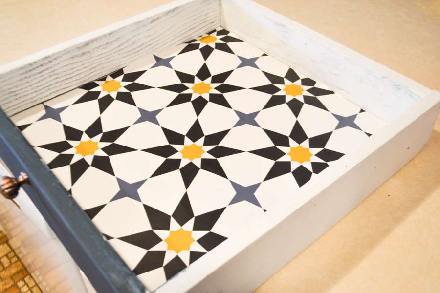 A completed lined drawer with a blue, yellow and white patterned wallpaper liner