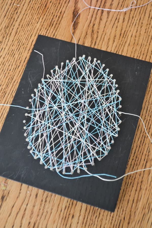 A close up of a black piece of wood with blue, purple and yellow string randomly strung over nails in the shape of an egg