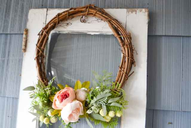 A grapevine wreath with pink peonies, ferns and other greenery on the bottom of a grapevine wreath against a white door