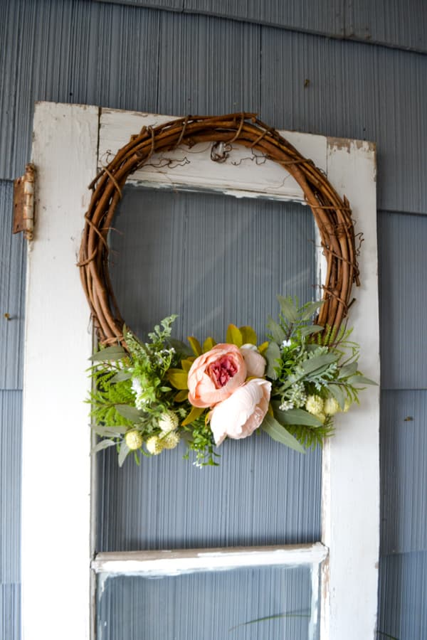 A grapevine wreath with pink peonies and other greenery against an old white door with a blue background