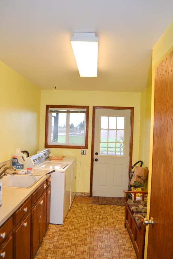 A laundry room view from the door towards an exterior door with brown flooring, yellow walls, brown cabinets and flourescent lighting