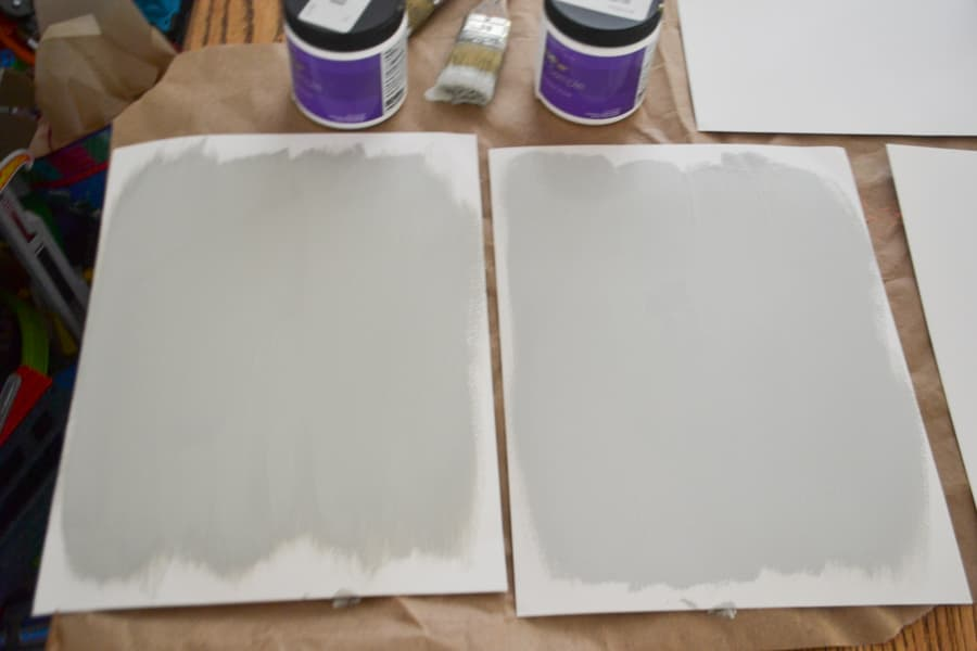 A close up of two white papers painted with gray shades of paint with open paint sample cans sitting above the papers