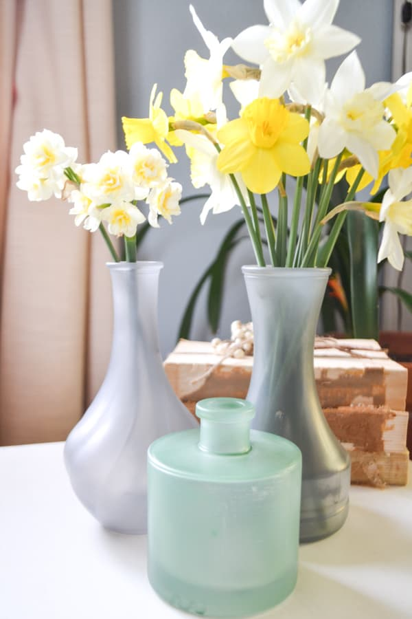 A close up of a cluster of three bud vases, two gray in the back and a green one in the front with daffodils in the gray vases