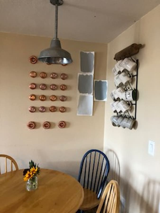 Four paint samples painted on paper hung on a wall above a kitchen table with a mug rack on the right and a copper display on the left