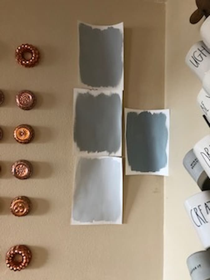A close up of four paint colors painted on white paper hung against a tan colored wall