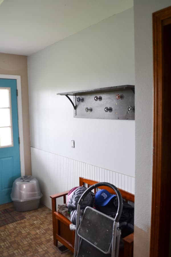 A gray wall with a brown floor and a bench in the foreground with a teal door in the background and a coat hook shelf above the bench