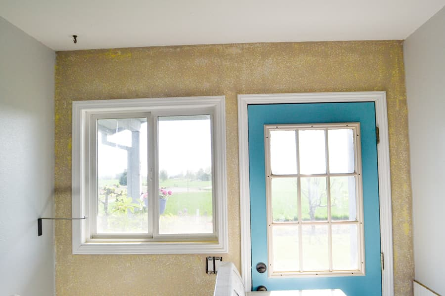 A view of a brown and white wall with a blue door on the right and window on the left