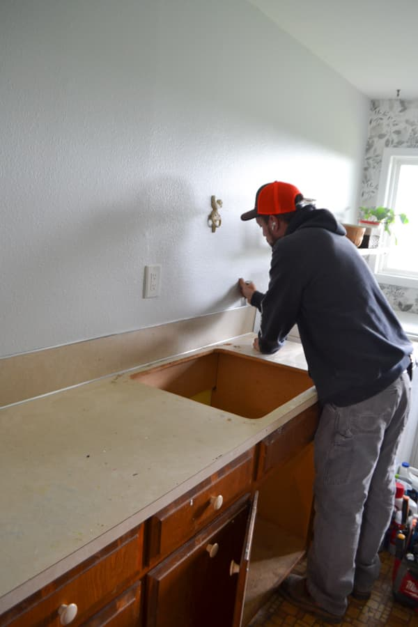 A man removing a laminate backsplash on a countertop