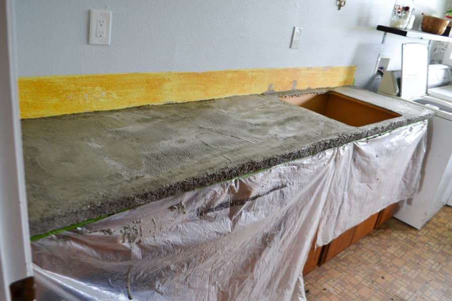 A gray concrete countertop with plastic hanging over the cabinets