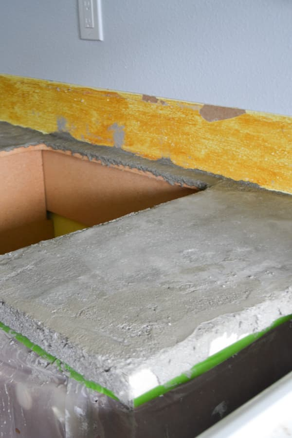 A close up of a light gray countertop with a sink hole to the left and a yellow wall part